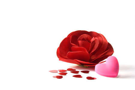 room for text: Close up of red paper rose, pink heart and heart confetti. Isolated on white. Copy space.