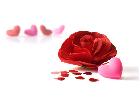 Close up of red paper rose, pink heart and heart confetti  Isolated on white  photo