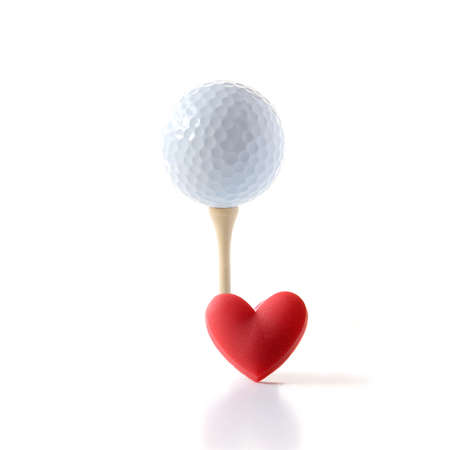 Studio image of white golf ball on a wooden tee with a red heart shape  Concept image for  Standard-Bild