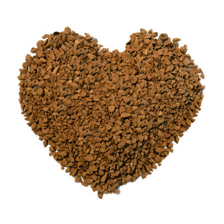 comprising: Studio macro image of a heart shape comprising instant coffee granules on a white background. Copy space.