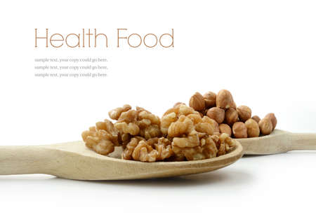 Studio image of fresh walnuts and hazelnuts on wooden spoons with soft shadows against a white surface. Copy space. photo