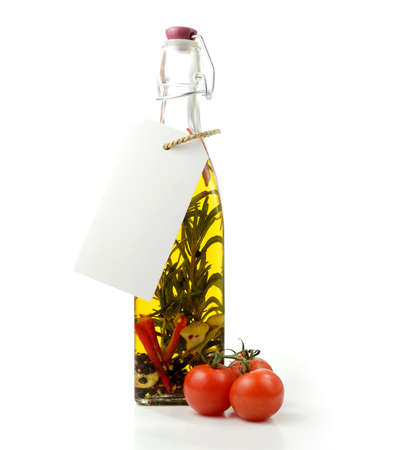 Studio image of home-made aromatic olive oil bottle with tomatoes against a white background. Blank label for your own text. Copy space. photo
