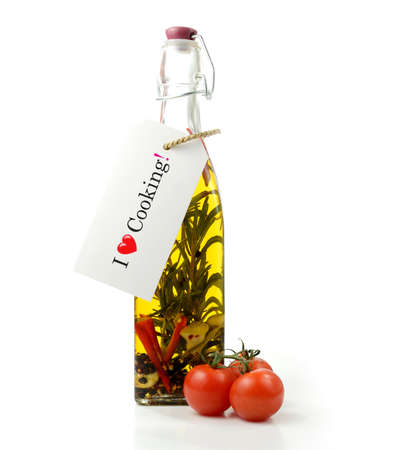 Studio image of home-made aromatic olive oil bottle with tomatoes against a white background. Label with  photo