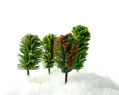 Studio macro of four model trees in deep snow against a white background  Copy space  photo