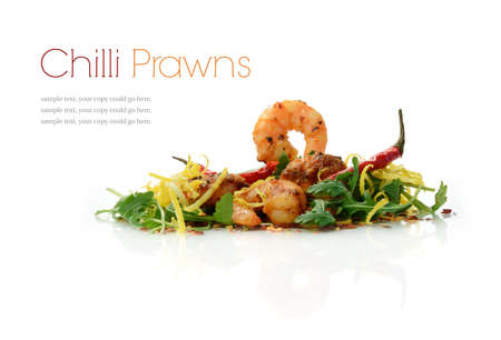 sizzling: Studio macro of sizzling chilli King Prawns served on a bed of fresh wild rocket leaves on a reflective surface against a white background. Copy space. Stock Photo
