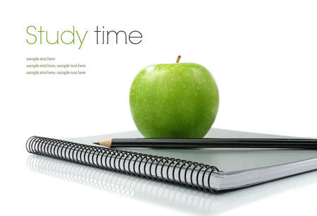 education: Studio macro of shiny green apple, pencil and new notebook on a white surface. Copy space. Stock Photo