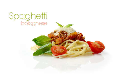 Studio macro of Spaghetti Bolognese meal with basil leaves, grated parmesan cheese and tomatoes.