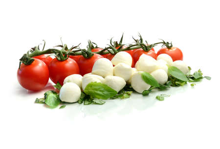 Studio macro of ripe tomatoes and mozzarella balls garnished with chopped basil. Copy space. photo