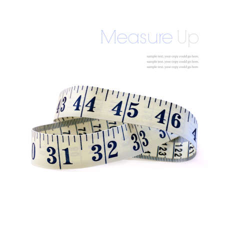 Studio macro of flexible tape measure against a white background with soft shadows. Copy space. photo