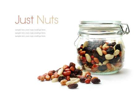 Studio macro van gemengde noten en gedroogd fruit in een pot naast een hoop noten op een witte achtergrond met zachte schaduwen