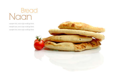 Studio macro of stacked freshly made Indian naan bread with tomatoes against a white background. Copy space. photo