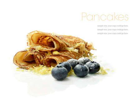 Studio macro of fresh cooked golden pancakes with blueberries and grated lemon rind against a white background. Copy space. Stock Photo - 17847832