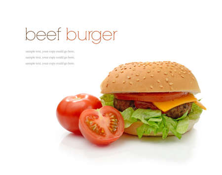 Home-made beef burger in a sesame seeded bun with lettuce, tomato and ketchup against a white background with soft shadows. Copy space. photo