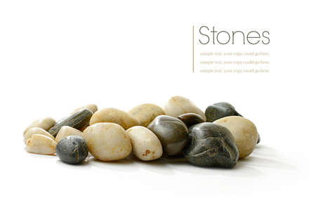 white pebble: Studio macro of neutral colored stones with soft shadows on a white surface. Copy space.