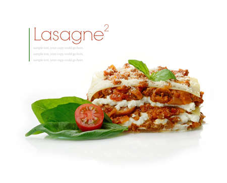 Studio macro of freshly prepared lasagne, basil leaves and tomatoes with soft shadows on a white surface. Copy space.