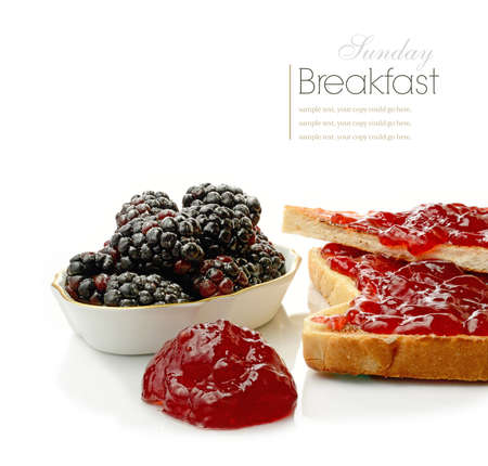 smothered: Studio macro of fresh toast smothered in strawberry jam on a breakfast table setting with soft fruits on a white surface. Copy space.