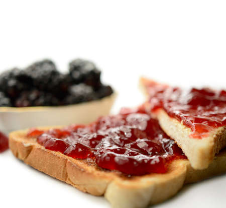 Macro of generous topping of strawberry jam on golden toast. Differential focus. Copy space. photo