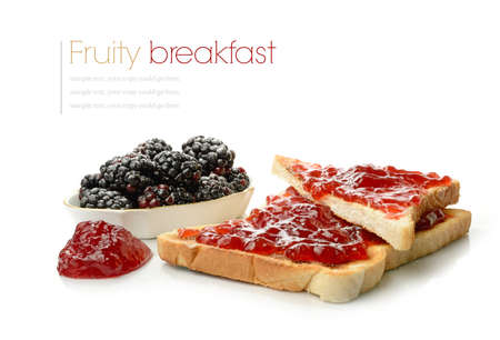 Studio macro of strawberry jam on toast and blackberries with soft shadows on a white surface. Copy space.