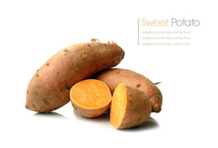 Studio macro of stacked sweet potatoes with soft shadows on a white surface. Copy space.