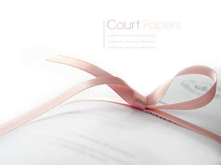 proceedings: Studio macro of legal court papers tied with pink ribbon with soft shadows on a white surface. Copy space. Stock Photo