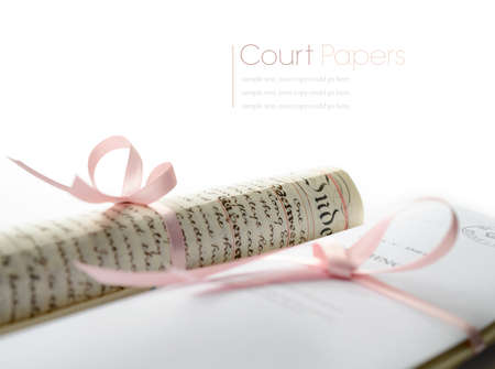 Studio macro of legal court papers tied with pink ribbon with soft shadows on a white surface. Copy space. photo