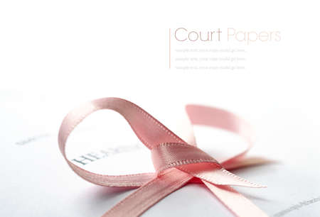 court proceedings: Studio macro of legal court papers tied with pink ribbon with soft shadows on a white surface. Copy space. Stock Photo