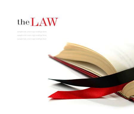 Law concept stock image. Silk ribbons on a opened legal book against a white background.