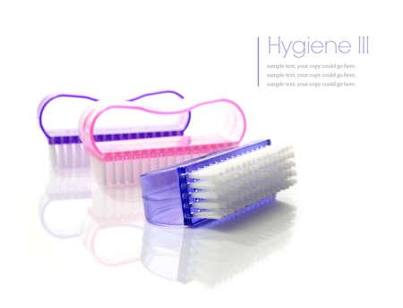 manos limpias: Concepto de higiene Imagenes almacenadas. Macro estudio de uñas, cepillos de plástico de colores sobre una superficie blanca.