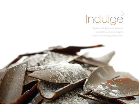 shards: Studio macro of sugar frosted dark chocolate shards against a white background. Differential focus. Copy space. Stock Photo