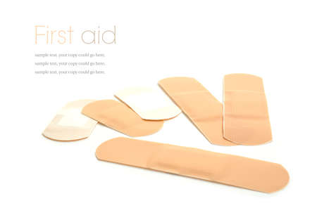 white bandage: Concept image for first aid. Sterile plasters against a white background. Copy space.