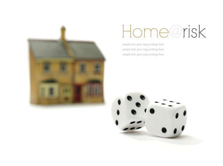 bad economy: Investment risk concept stock photograph. Rolling dice and property against a white background. Copy space.
