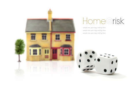 Investment risk concept stock photograph. Rolling dice and property against a white background. Copy space.