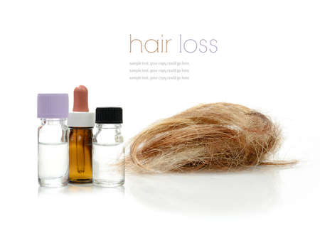 loss: Concept image depicting alternative treatments for hair loss with medication bottles and hair piece against a white background. Copy space.