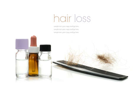 calvicie: Concepto de imagen que representa a los tratamientos alternativos para la pérdida de cabello con frascos de medicamentos y el peine sobre un fondo blanco el espacio de copia Foto de archivo