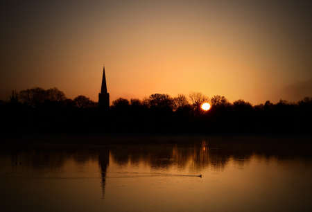 neighbouring: Spring morning sunrise over English nature reserve with neighbouring village church. Copy space. Stock Photo