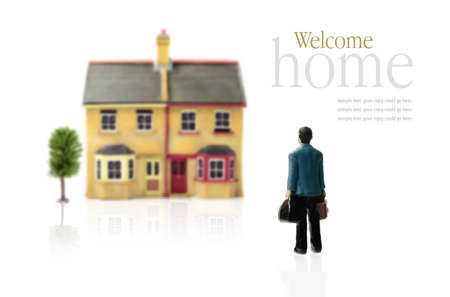 Concept stock photograph depicting coming home  Man carrying cases approaching property against a white background  Copy space