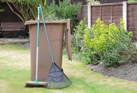 Stock image of garden waste in recycling container with lawn rake and sweeping brush in pleasant garden  Standard-Bild