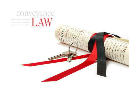 Concept image depicting conveyance law with legal scroll and house keys against a white background. Copy space.
