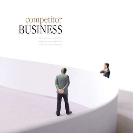 divided: Business concept image depicting a competitor situation. Two businessmen divided by a wall. Copy space. Stock Photo