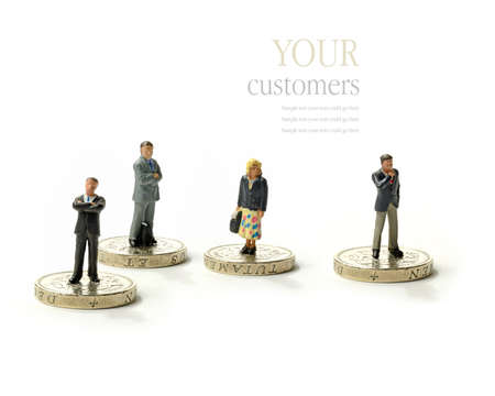 Concept image for your paying customers. Men and women standing on golden coins against a white surface and background. Copy space.
