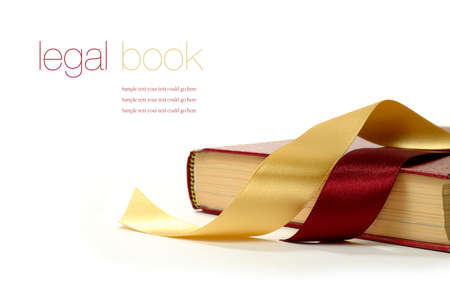 Stock photograph of legal concept, old book with legal ribbon ties on a white surface. Copy space. photo