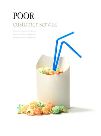 ha: Oops! Fresh popcorn in a container with drinking straws. Funny concept image for poor customer service, mistake, error, etc. Copy space.