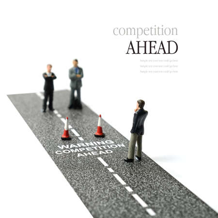 business competition: Business concept image depicting competitors waiting ahead. Selective focus on the road text. Copy space.