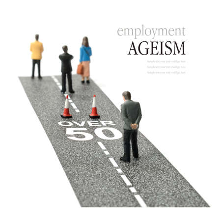 prejudice: Concept image depicting employment ageism and discrimination for people over fifty. Selective focus on the road text. Copy space.