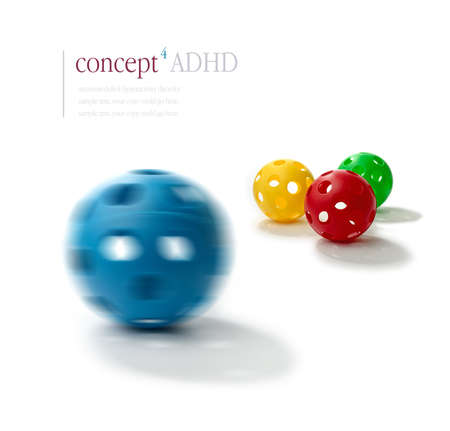 Concept image illustrating Attention Deficit Hyperactivity Disorder (ADHD). Spinning blue plastic ball with the illusion of two eyes and a mouth in foreground with normal balls in sharp relief in background. ADHD concept. Copy space. Standard-Bild
