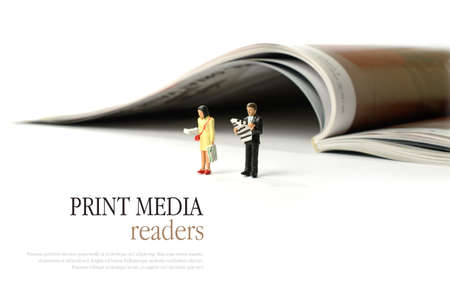magazine reading: A media concept image of two  business newspaper readers against a magazine in background. Copy space.