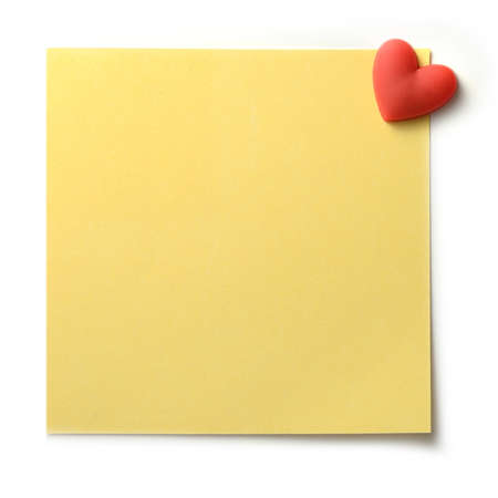 yellow heart: Studio macro of textured yellow post note pinned to a white background with a red heart shaped pin. Copy space.