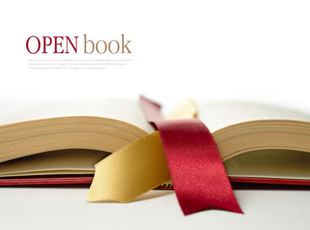 Stock photograph of legal concept, open old book with legal ribbon ties on a white surface. Copy space. Stock Photo