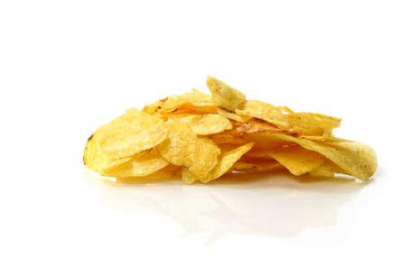obesidad infantil: Estudio macro de papas fritas (o chips) en una superficie blanca sobre un fondo blanco. Copiar el espacio.