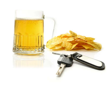 under arrest: Studio macro of pint of beer, scattered potato chips (crisps) and car keys on a white surface. Concept image for drink driving. Copy space.